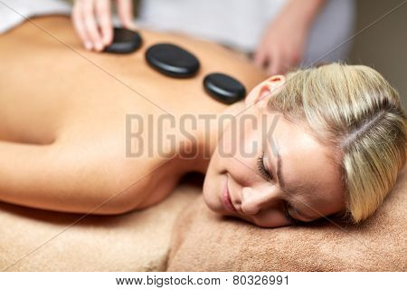 people, beauty, spa, healthy lifestyle and relaxation concept - close up of beautiful young woman having hot stone massage in spa