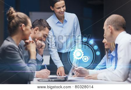 business, technology, deadline, management and people concept - smiling female boss talking to business team in office late night