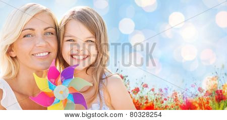 summer holidays, family, children and people concept - happy mother and girl with pinwheel toy over blue lights and poppy field background