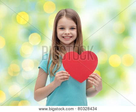 love, charity, holidays, children and people concept - smiling little girl with red heart over green lights background