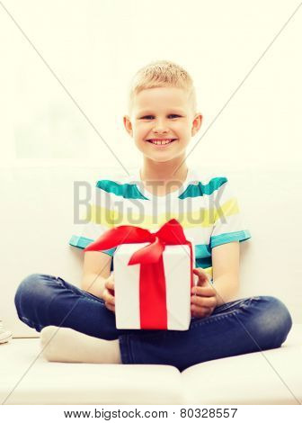 leisure, childhood, holidays and home concept - smiling little holding gift box with red bow and sitting on couch