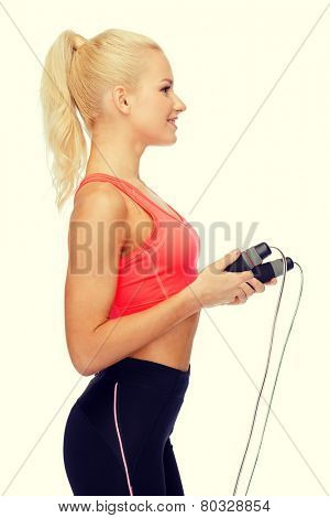 sport, exercise and healthcare - smiling sporty woman with skipping rope