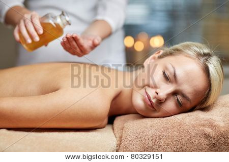 people, beauty, spa, healthy lifestyle and relaxation concept - close up of beautiful young woman lying with closed eyes on massage table and therapist holding oil bottle in spa