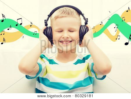 home, leisure, technology and music concept - smiling little boy with headphones at home