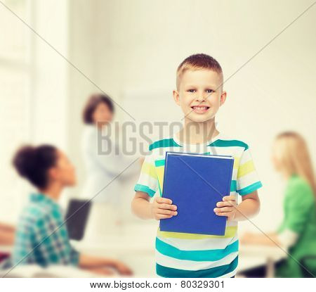 education, childhood, teamwork and school concept - smiling little student boy with blue book over group of students in classroom