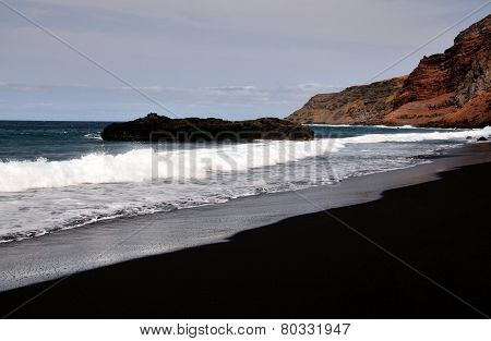 Empty Black Sand Beach Under A Cliff