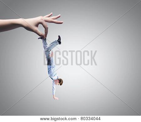 Close up of big human hand catching businessman