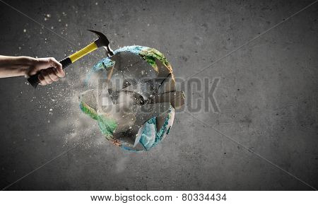 Close up of hammer in human hand hitting Earth planet. Elements of this image are furnished by NASA
