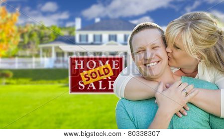 Happy Couple Hug In Front of Sold Real Estate Sign and Beautiful New House