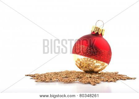 Christmas bauble resting on a golden snowflake, focus on the reflection on the bauble; on white