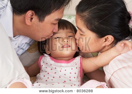 Parents Kissing Daughter