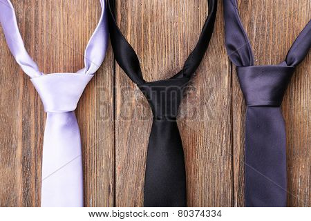 Trendy ties on wooden planks background