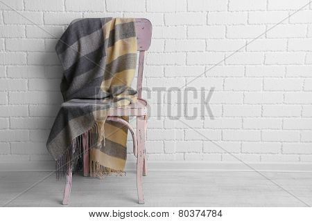 Modern interior with chair and plaid on it on white brick wall background