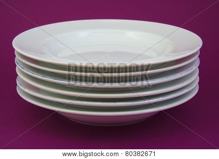 Stack of white and used dishes on purple background.