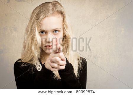 Blond Teenage Girl Pointing Finger Gun At The Camera