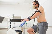 image of exercise bike  - Man doing fitness test on exercise bike at the medical centre - JPG