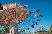 picture of carnival ride  - Action photo of carousel on blue sky - JPG