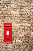 stock photo of old post office  - traditional old English red postbox mounted in a cotswold stone wall - JPG