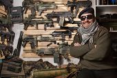 pic of beret  - Arms merchant in the beret and sunglasses on the weapon display background - JPG