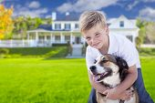 stock photo of dog eye  - Happy Young Boy and His Dog in Front Yard of Their House - JPG