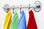 stock photo of pinafore  - colored towels hanging on the rack in the bathroom - JPG