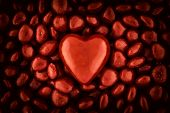 picture of valentine candy  - A close up of a pile of red valentines candy with a large red heart shaped candy sitting on top in the middle of the image - JPG