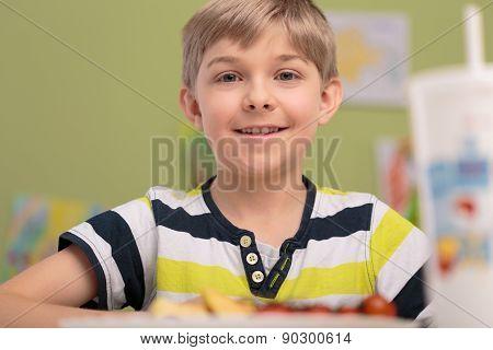 Boy Eating Breakfast In Classroom