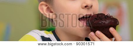Schoolchild Eating Chocolate Muffin