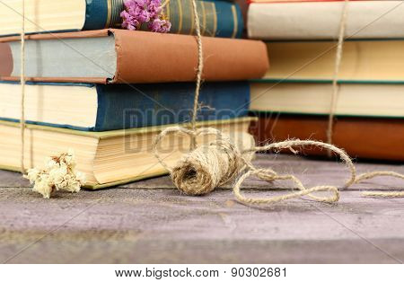 Stacks of books with dry flowers and twine on table close up