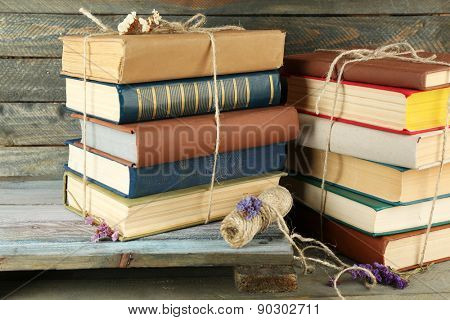 Stacks of books with dry flowers and twine on wooden background