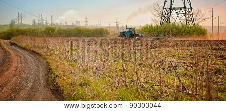 Tractor Ploughing A Field With A Trail Of Dust