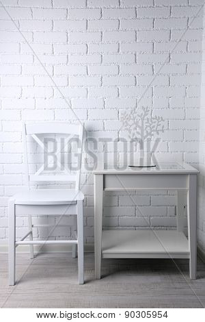 Chair and nightstand on white brick wall background
