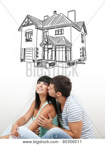 Dreaming concept. Beautiful loving couple sitting on floor in room