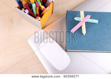 Books, computer mouse and pieces of chalk on wooden table background