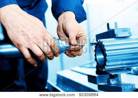 Man working on drilling and boring machine in workshop. Industry, industrial concept.