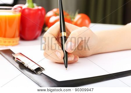 Nutritionist Doctor writing  diet plan in office, closeup