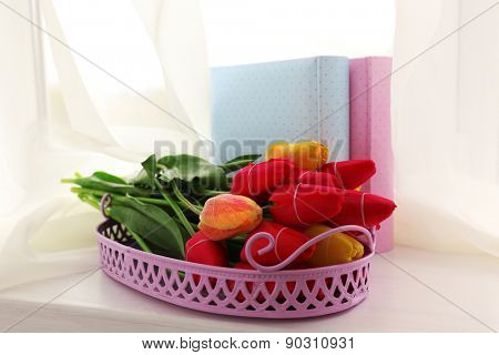 Still life with bouquet of fresh tulips on windowsill background