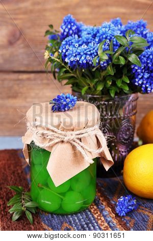 Blue bell flowers with lemon and maraschino cherry in glass jar on wooden background