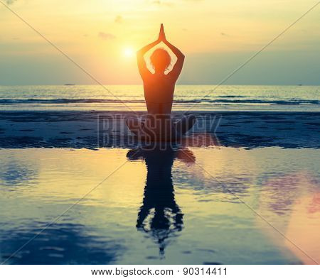 Silhouette of yoga woman on sea sunset in bright colors, reflection in the water.