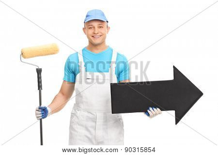 Young male decorator in a white uniform holding a paint roller and a big black arrow pointing right isolated on white background