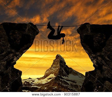 Silhouette girl climbs on a rope over an abyss. In the background Matterhorn at sunset.