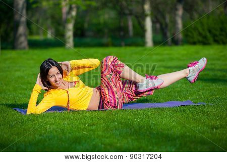 Exercising fitness woman sit ups outside during crossfit exercise training. Happy fit girl doing sid