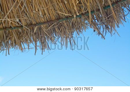 Detail of straw parasol and blue sky