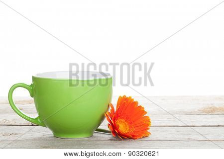 Cup of coffee and gerbera on wooden table with copy space