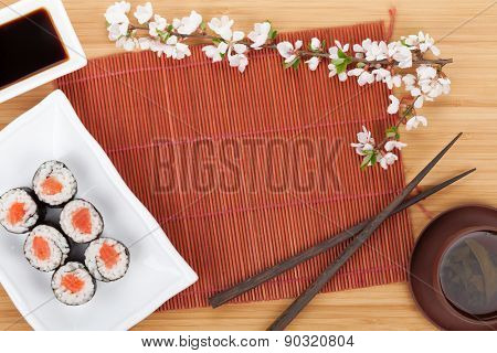 Sushi maki set, green tea and sakura branch over bamboo table with copy space