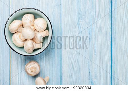 Fresh champignon mushrooms on blue wooden table with copy space