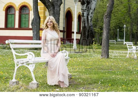 Blond Woman In Evening Gown Sitting On White Bench