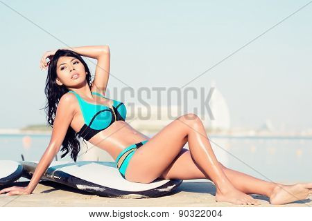 Surfer girl close to water on city beach on surf board