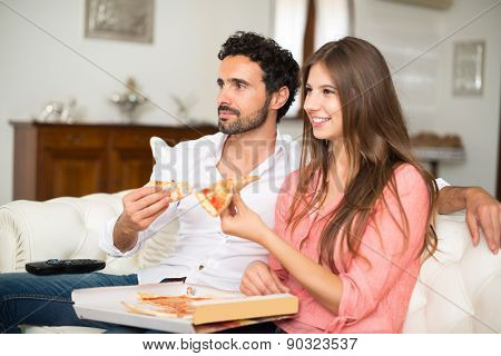 Happy couple watching tv while eating pizza. Shallow depth of field, focus on the man