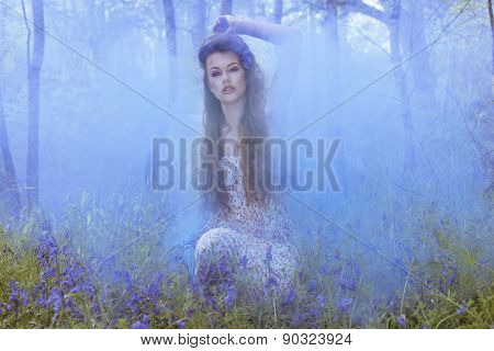 Artistic portrait of a girl surrounded by smoke in blue